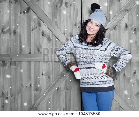Beautiful  young happy  smiling woman wearing winter hat and gloves covered with snow flakes. Christmas portrait concept.