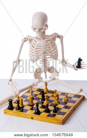 Skeleton playing chess game on white