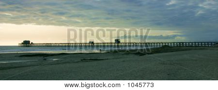 Cloudy Beach And Pier Scene