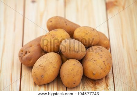 Raw potatoes on a wood table