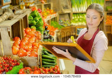 Woman writing sign for fruit and veg