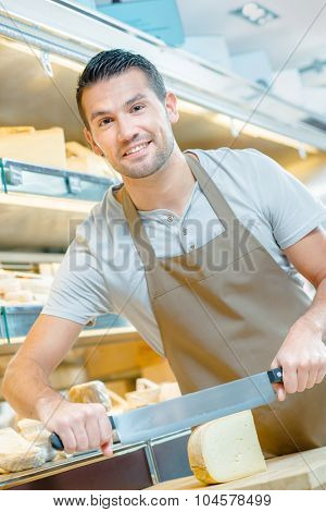 Man cutting cheese for a customer