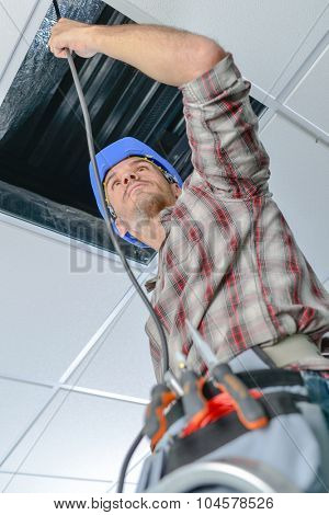 Electrician repairing wiring in an office