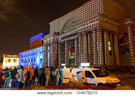 ST. PETERSBURG, RUSSIA - OCTOBER 8, 2015: People watching laser show on the facade of the theater Baltic House during LumiFest. It was the first festival of light culture in Russia