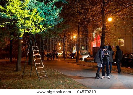 ST. PETERSBURG, RUSSIA - OCTOBER 8, 2015: People looking photos of light installation in the Alexander garden during LumiFest. It was the first festival of light culture in Russia