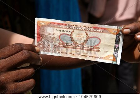 LABADEE, HAITI - SEPTEMBER 27, 2015: An unidentifiable Haiti resident displays Haitian Money to show their currency. Labadee, Haiti