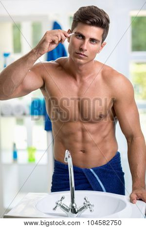 Man removing eyebrow hairs with tweezing front of mirror