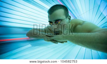 Man with protect glasses on tanning bed in solarium