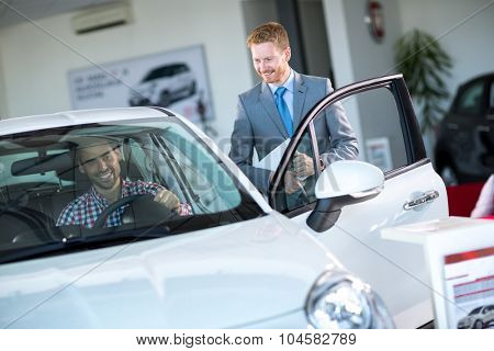 friendly car dealer showing new car to male customer