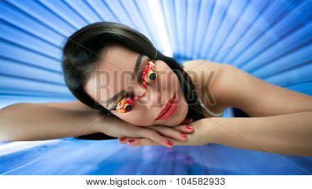 Girl with protect glasses in solarium enjoy in treatment