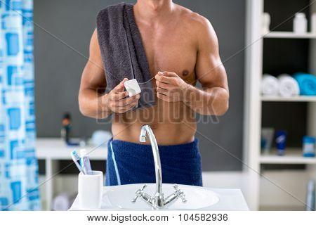Handsome male preparing dental floss, in bathroom