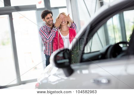 Couple stand in front of new car, man holding his wife covered her eyes