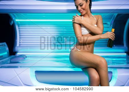 Attractive  young woman preparing for tanning in solarium, using sun cream before tanning