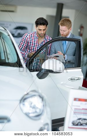 Car agent showing vehicle male client at car dealership saloon
