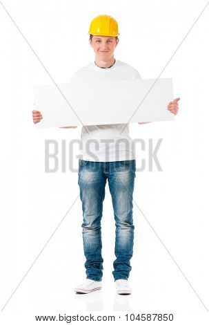 Smiling young businessman in hard hat showing blank placard board, isolated on white background