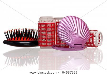 Set of cosmetics - hairbrush, hair curlers and small mirror, isolated on white background