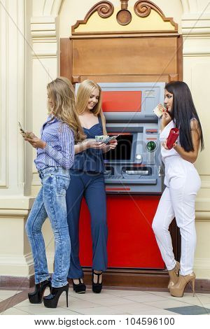 Three young beautiful modern girls using an automated teller machine. Women withdrawing money or checking account balance
