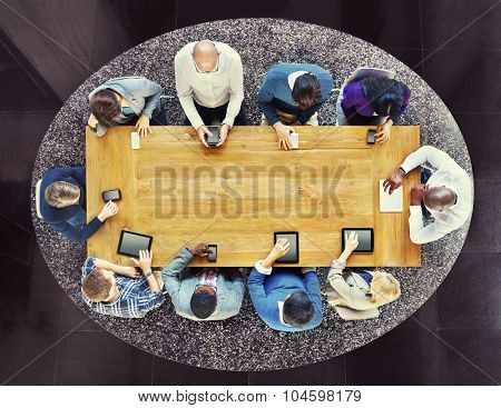 Group of Diverse People in a Table Using Devices Concept