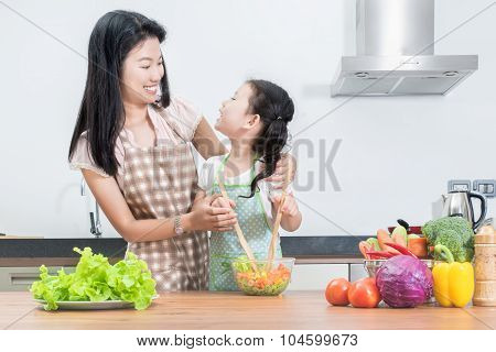 Family, Children And Happy People Concept - Asian Mother And Kid Daughter Cooking In The Kitchen At