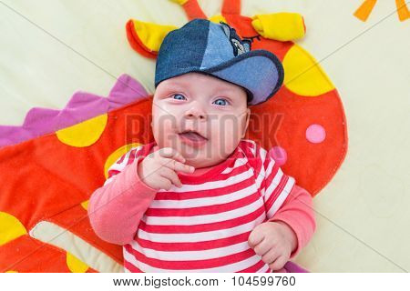 Baby girl in blue hat posing at the camera