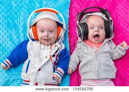Happy twin babies listening to the music on headphones