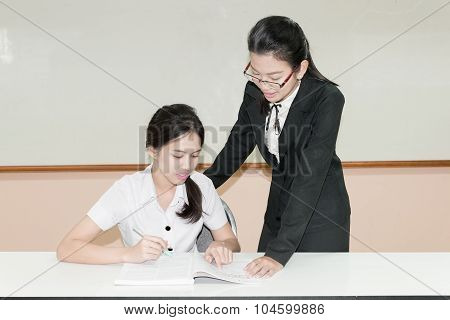 Teacher Guide Something To Asian Student In Uniform At Classroom