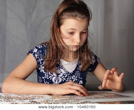 Teenage girl doing puzzle