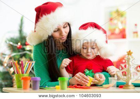 Mother and little girl preparing Christmas decor.