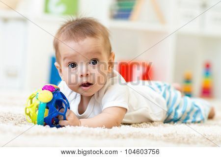 Joyful baby lying on the carpet in nursery room