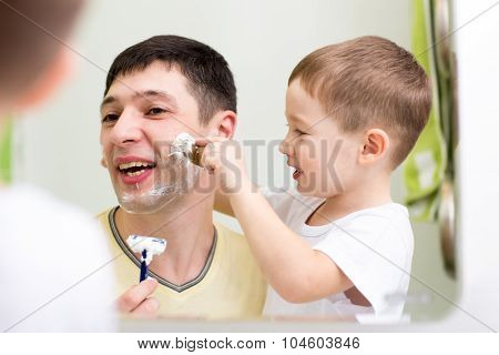 Father and child son shaving together at home bathroom