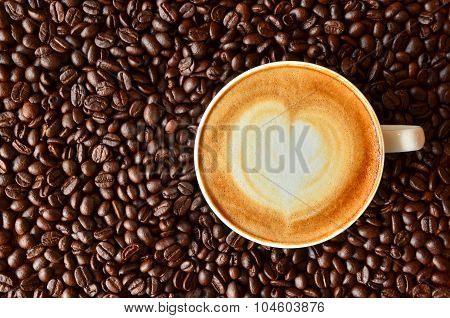 A Cup Of Coffee With Heart Shape On Coffee Bean Background