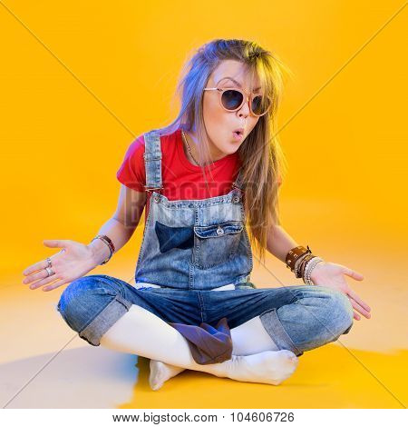 Portrait Of Funny Girl Sitting With Glasses On A Yellow Background