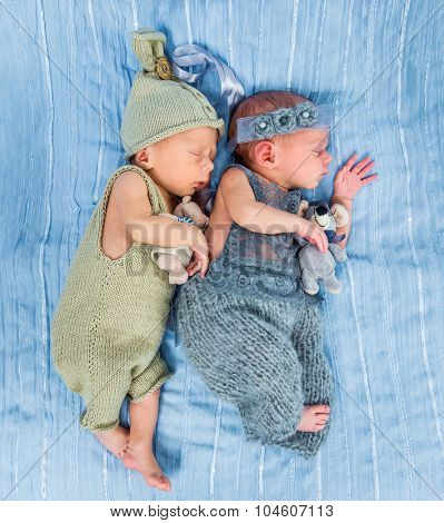 newborn twins  sleeping with toys on a blue blanket