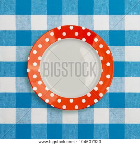 Polka dot red white dinner plate on blue checked tablecloth