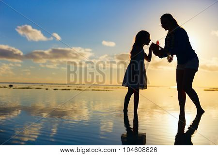 Silhouettes of mother and daughter at tropical beach during sunset