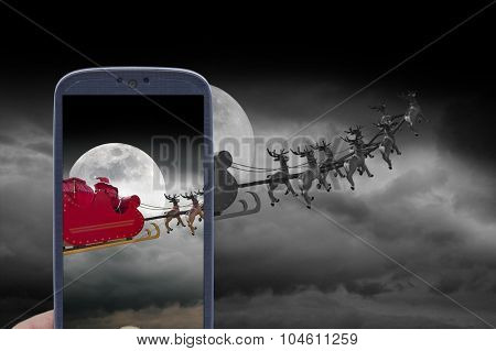 Santa Claus riding a sleigh led by reindeers caught by smartphone shot