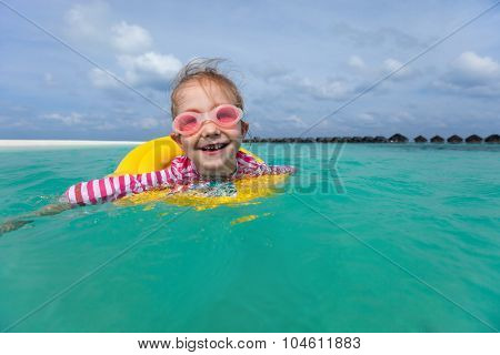 Adorable little girl with yellow inflatable ring swimming in a tropical ocean on summer vacation