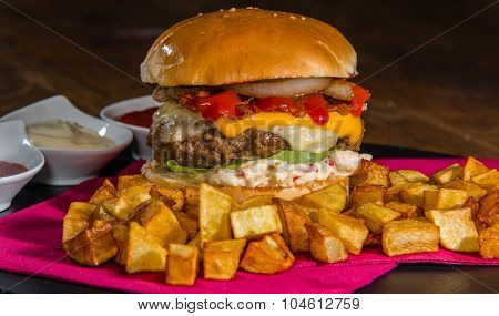 Large burger served with crispy baked potatoes