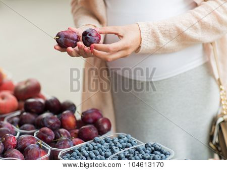 sale, shopping, pregnancy and people concept - close up of pregnant woman choosing plums at street food market