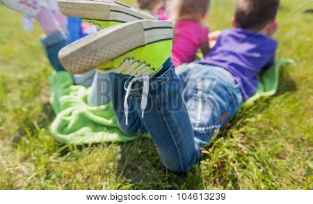 summer, childhood, leisure and people concept - close up of happy kids lying on picnic blanket outdoors