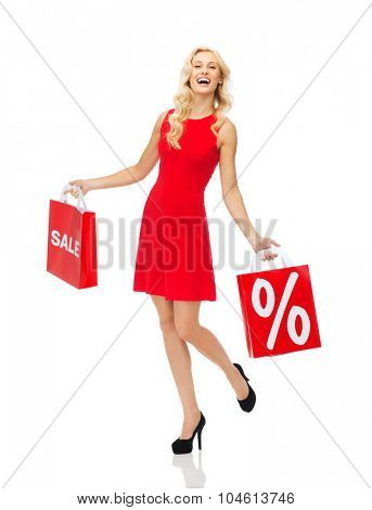 people, sale, discount and holidays concept - smiling woman in red dress with shopping bags