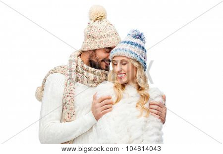 winter, fashion, couple, christmas and people concept - smiling man and woman in hats and scarf hugging