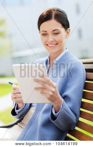 business, paperwork and people concept - young smiling businesswoman reading notes in notepad and sitting on city bench