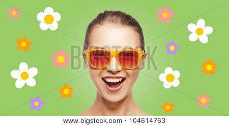people, summer holidays and pop art concept - happy screaming teenage girl in shades over green background with flowers