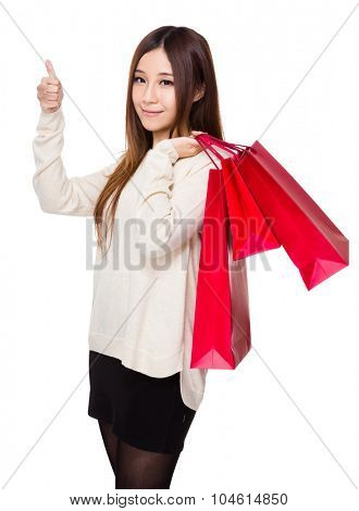 Asian woman showing with shopping bag and thumb up