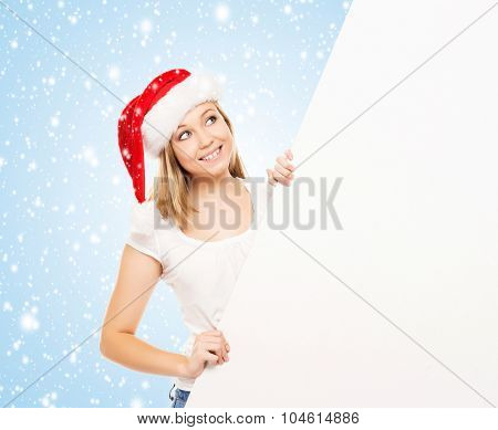 Young and attractive teenager girl with a blank billboard over blue background with snowflakes