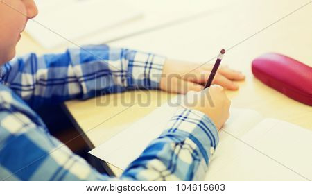 education, elementary school, learning and people concept - close up of little schoolboy with notebook and pencil writing test at school