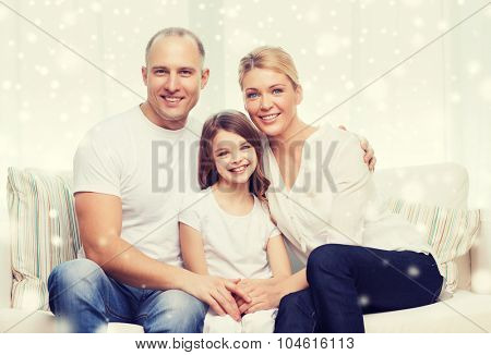 family, childhood, people and home concept - smiling parents with little girl sitting and hugging at home