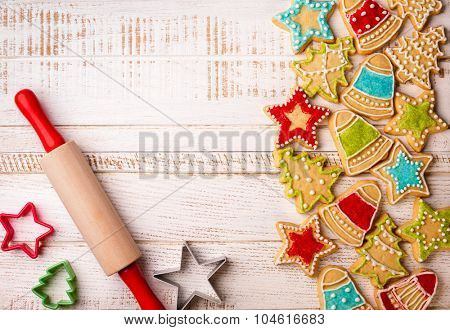 Christmas cookies, rolling pin and cookie cutters on the wooden background