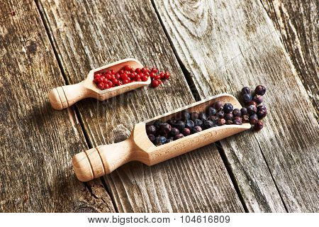 Wooden scoops with dried juniper berries and rose pepper over rustic background